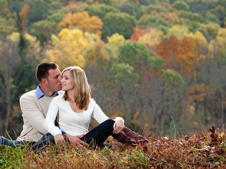Beautiful couple sitting infront of picturesque fallscape with yellow, orange and red leaves.