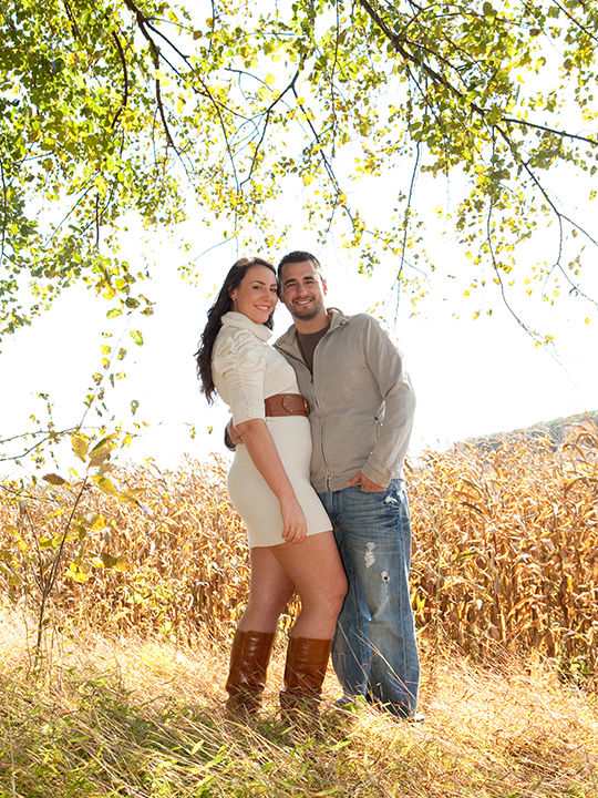 Relaxed couple standing in a field of corn posing together for engagement