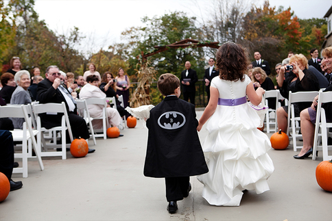 Ring bearer walking down the aisle in Batman cape and sweet flower girl holding hands.