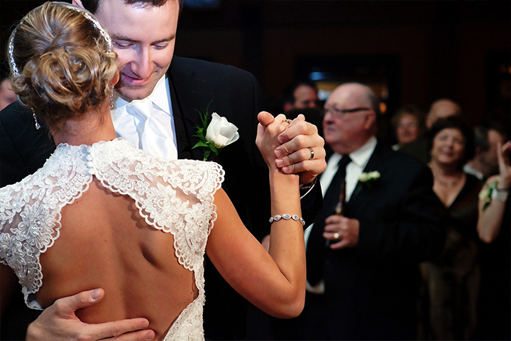 Closeup of husband holding wife and her lacy, open back wedding dress.