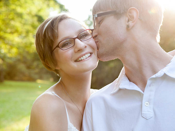 Sunlit fiance kisses his fiancee while she smiles at the camera