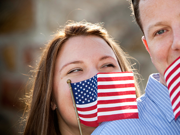 Patriotic couple joke around with one another while holding American flags up looking lovingly at one another.