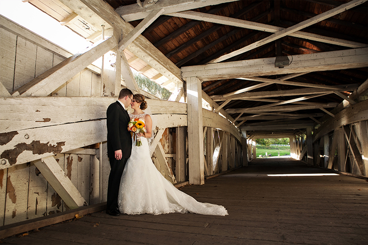 Romantic couple stand forehead to forehead on rustic covered footbridge.