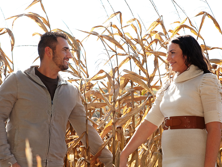 Couple look lovingly at one another, holding hands in front of corn stalks.