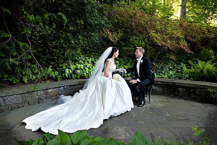 Bride and groom chat in a secret garden with an outstanding long wedding train that looks magical.