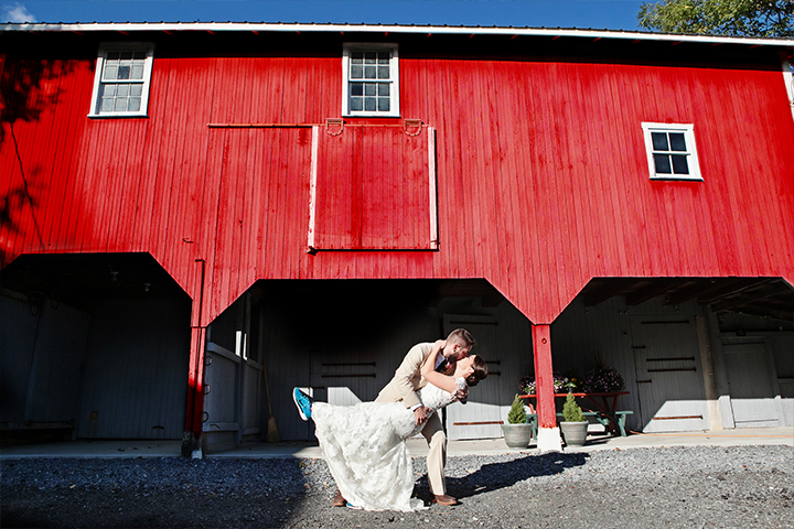 Unique bride and groom dip for a kiss outside rustic red barn