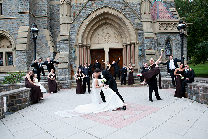 Groom dipping his bride for a kiss while bridal party cheers in the background outside of a church on the campus for Muhlenberg in Pennsylvania.