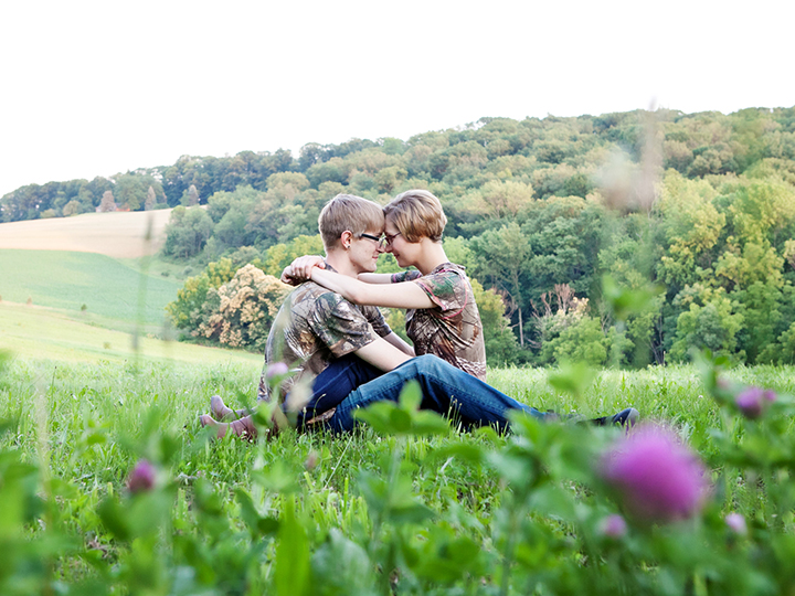 Loving embracing couple in rolling hills with cute purple flowers