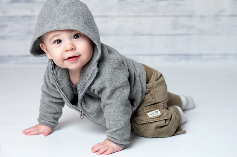 Sweet baby boy crawling in gray hoodie and khakis