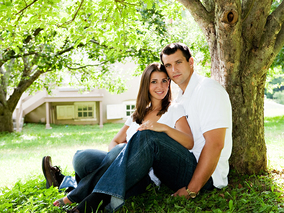 Attractive couple sit together at the foot of a tree for outdoor engagement shoot.
