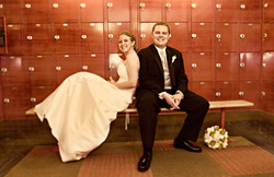 Fun loving couple sitting on bench inside of a gym locker room smiling at the camera