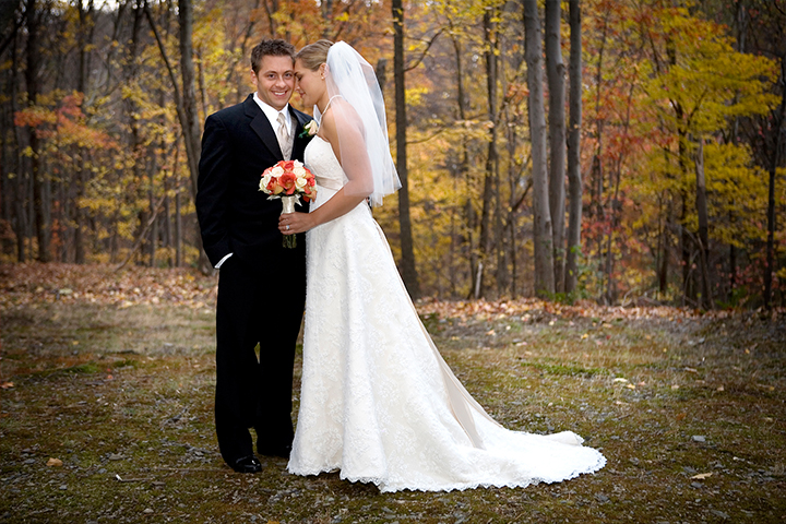 Autumn wedding couple nuzzle while groom smiles at photographer.