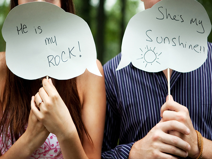 Couple holding signs - he's my rock and she's my sunshine.