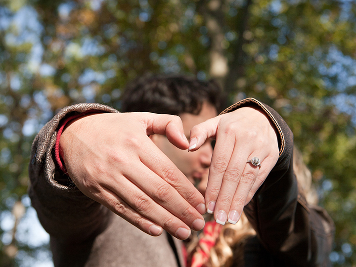 Newly engaged couples' hands form a heart while they remain in the background unfocused