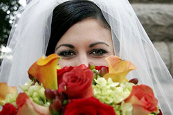 Bride excitedly nosing her bouquet before tossing it.