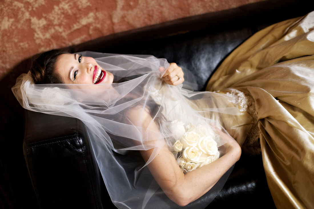 Laughing bride grasping her veil and white roses while leaning back on a black leather couch.