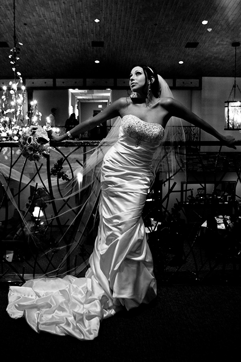 Sassy bride striking a pose in black and white, leaning against an ornate railing with a chandelier backdrop.