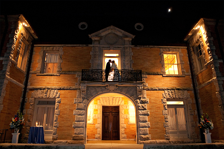 Spanish villa at night capturing bride and groom in an upstairs balcony, backlit and kissing.