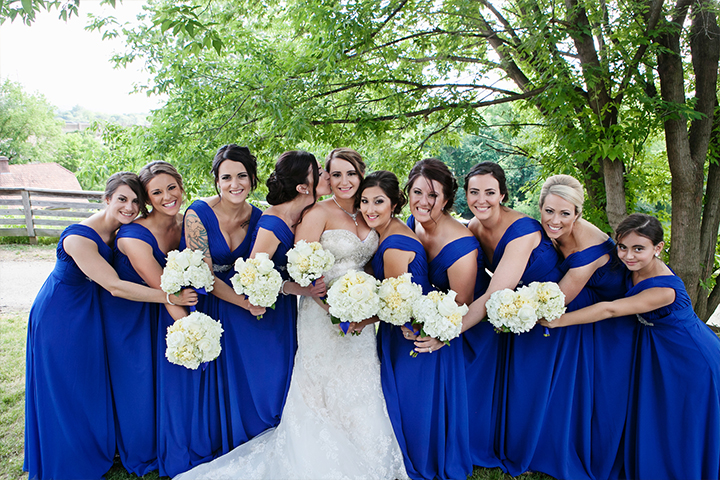 Lovely bride in the center of 9 bridesmaids all wearing bright blue bridesmaid dresses, standing outside beneath trees.