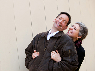 Woman hugs fiance from behind while they both laugh and smile.