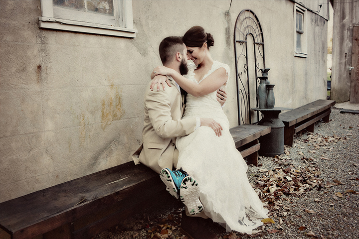 Bride sits atop grooms lap outside on a bench on wedding day.