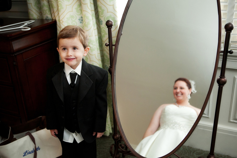 Son looks adoringly at his mother in her wedding dress, lovingly where behind him you can see his mom, the bride in the reflection of a full-length mirror staring back at him.