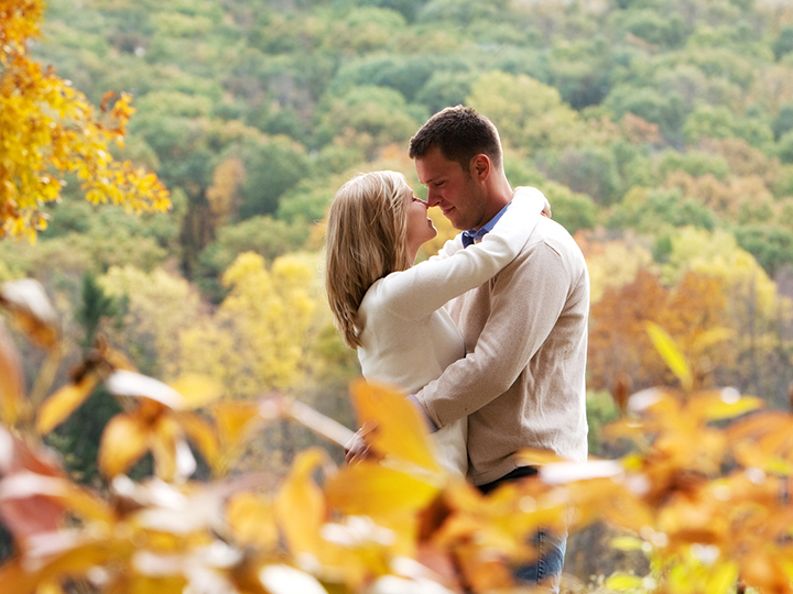 Secret photographer style image where leaves are in front of beautiful couple who are embracing