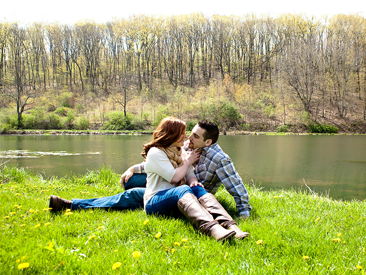 Romantic couple sitting beside stream in the grass