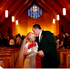 Bride and groom kissing in church after vows cited in testimonial