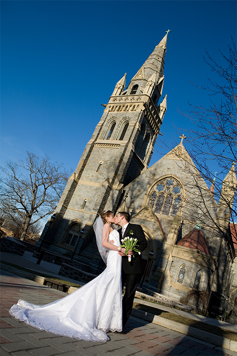 Leaning in for a big kiss in front of a cathedral - bride and groom kissing.