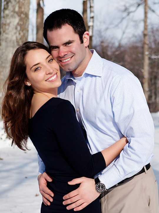 Photogenic couple embrace for engagement pictured outside in winter with incredible, white smiles.