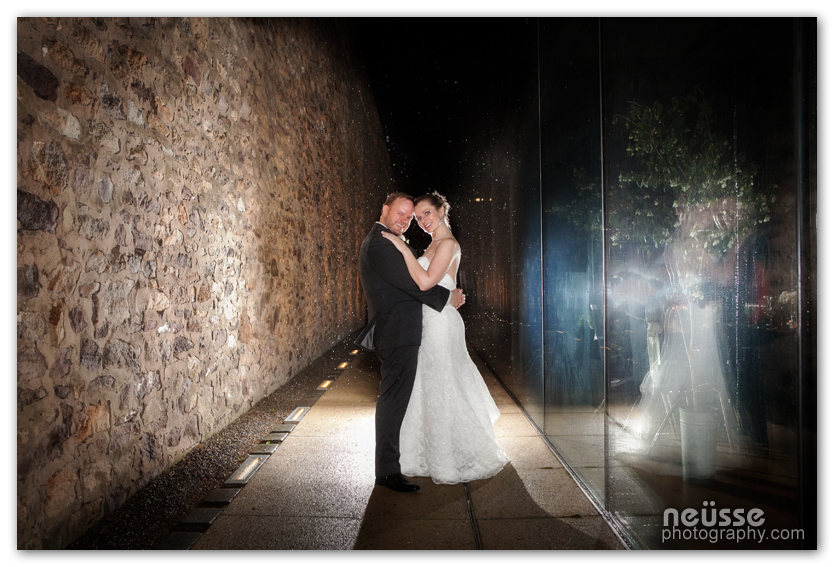 Spring Wedding Image of bride and groom at Michener Art Museum in Doylestown of Pennsylvania USA at night between stone wall and glass wall of the museum by Neusse Photography premier wedding photographer in Pennsylvania