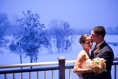 Romantic embrace on a snowy wedding day of husband and wife inside during their reception.