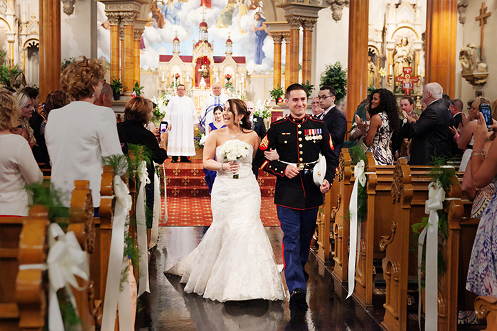 Military wedding couple exits the church after saying their vows, surrounded by friends and family.