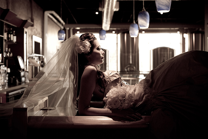 Vintage feel image of bride laying atop a bar in a wedding dress.