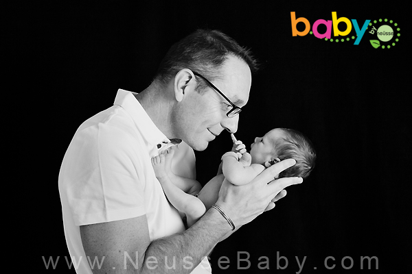 Father holding newborn while the baby boy points a finger at his father's nose in black and white portrait