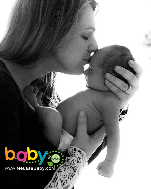 Picture of mother holding and kissing her newborn baby girl in black and white color