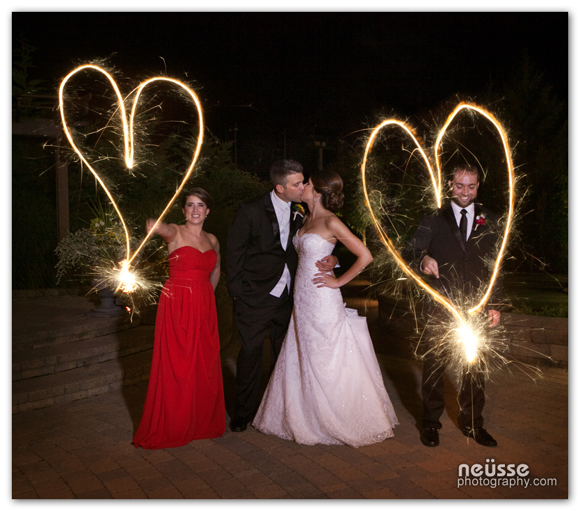 Night portrait at Bear Creek Mountain resort in Macungie in Lehigh County of PA with Maid of honor in red bridesmaid gown and best man drawing heart shapes with 3 foot long sparkles flanking newly wed bride and groom kissing in the middle