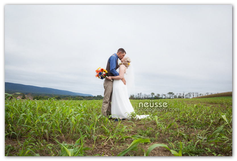 Picture of bride and groom kissing in open green field farm land and blue sky. Groom in khaki pants and blue shirt and vest