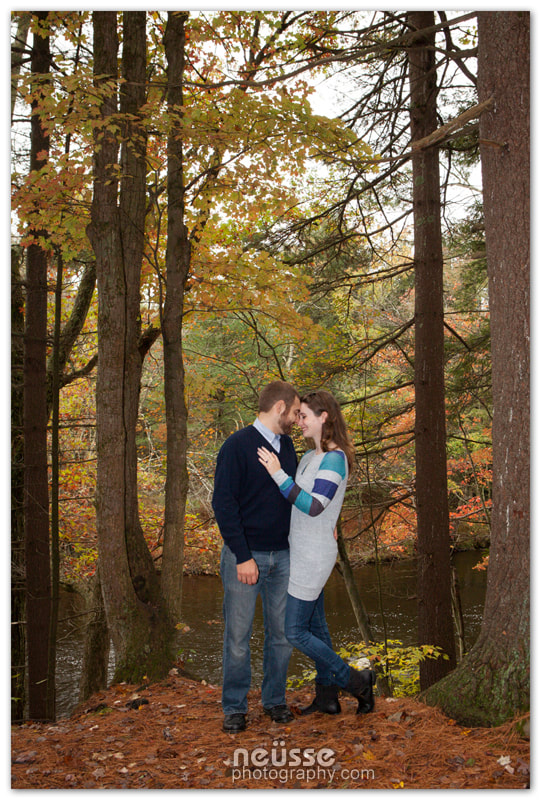 Picture of newly engaged couple with Autumn Fall foliage color in the background at Austin T Blakeslee Park Pocono PA