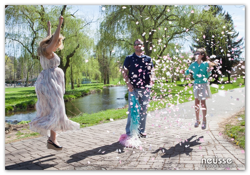 Picture of gender reveal at Allentown Rose Garden with black balloons popping to reveal the color of pink confetti while mother and daughter jumping with joy